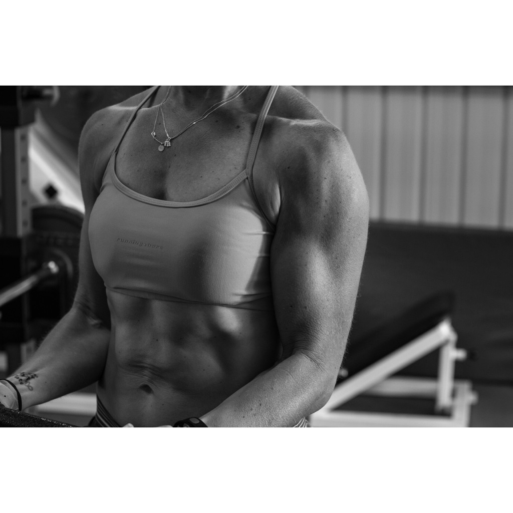 black and white picture of a woman in a crop top curling a bar to work her bicep muscles