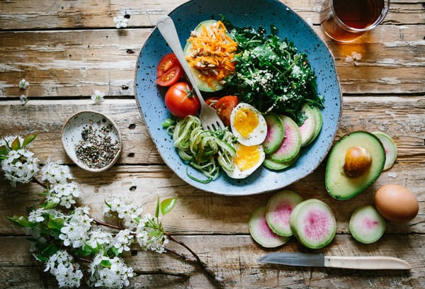 wooden table with blue dinner dish with sliced egg, cherry tomatoes, radish and cooked spinach with avocado cut in half and egg in shell sitting beside bowl.
