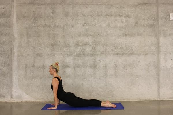 lady in black legging and top stretching on a blue yoga mat in front of a concrete wall