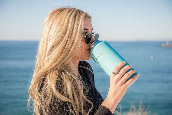 woman in a black long sleeve top drinking out of a blue water bottle with ocean in the background