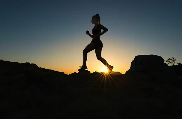 silhouette of woman running over rocky trails with sunrise in background