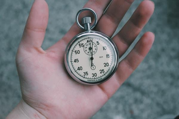 left hand opened with a stopwatch placed on palm of hand.