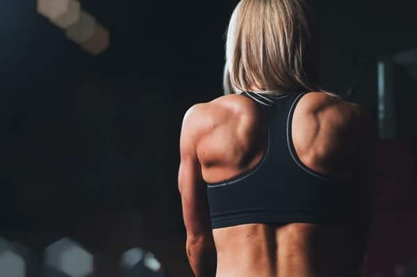 woman with blonde hair in black crop top with her back showing