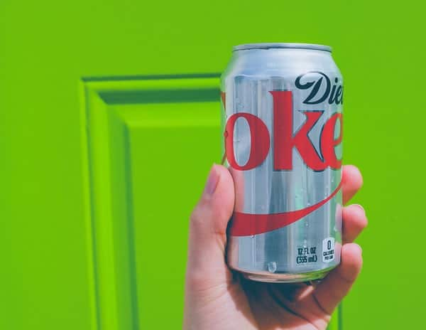can of diet coke held up in front of green door
